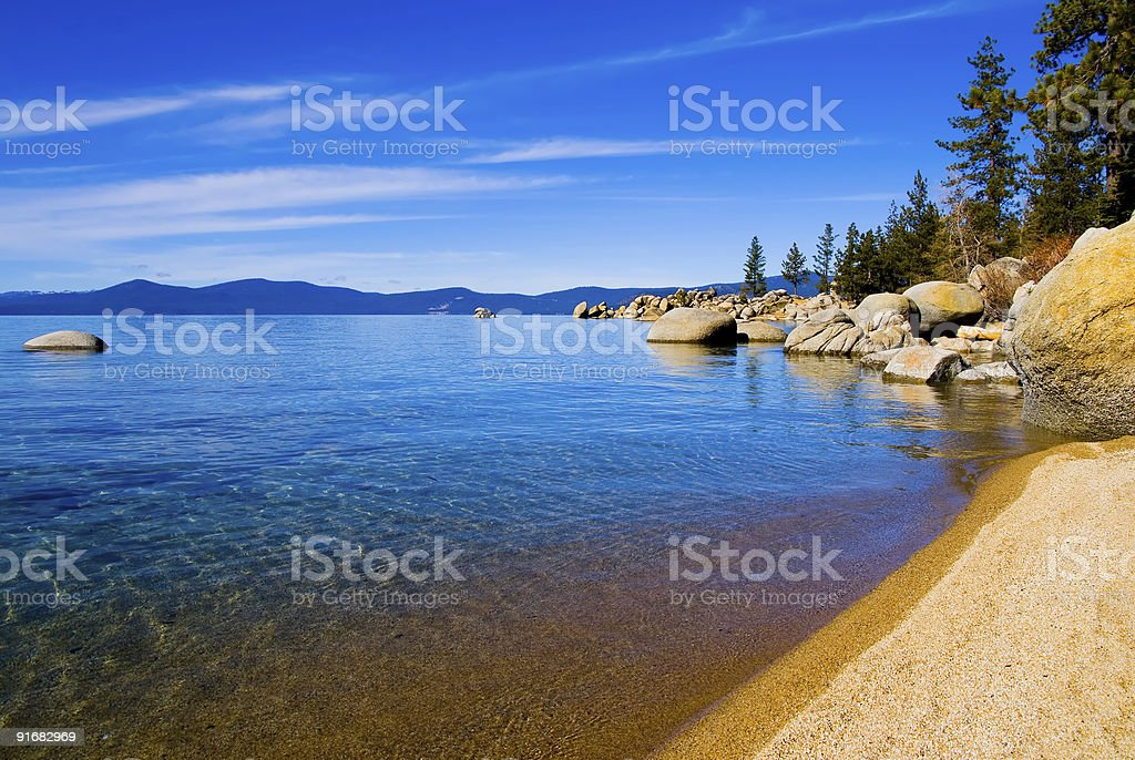 Lake reflecting the sky with rocks and mountains afar stock photo