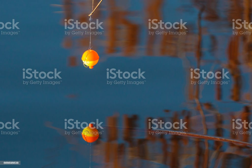 Lake reflection of a fishing hook, line and bobber stock photo