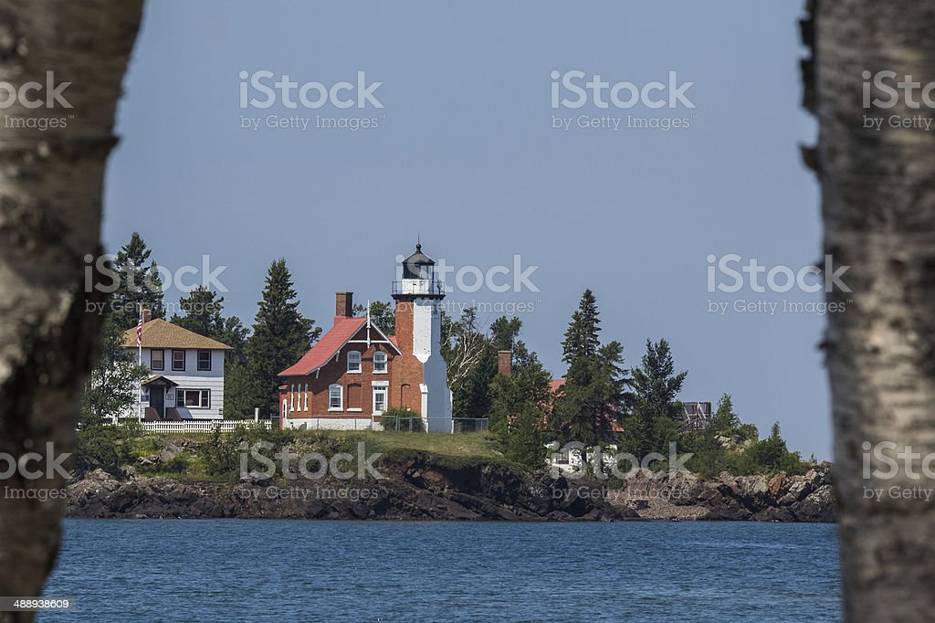 Lake Superior Lighthouse Framed by Birch Trees stock photo