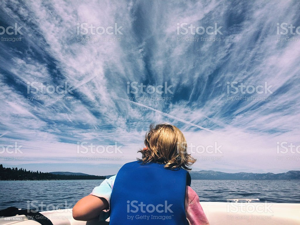 Lake Tahoe beauty with a boy in a boat stock photo
