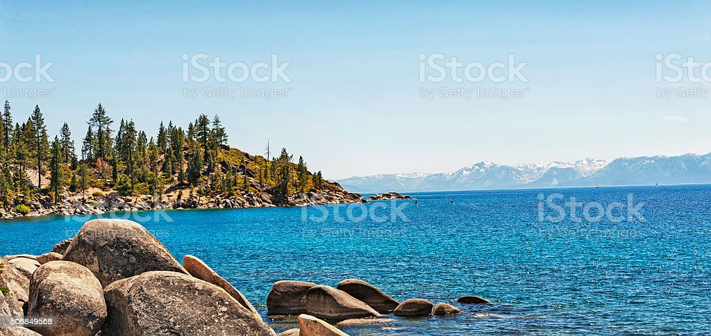 Lake Tahoe Bolders and Snow Covered Mountains with Paddle Boarders stock photo
