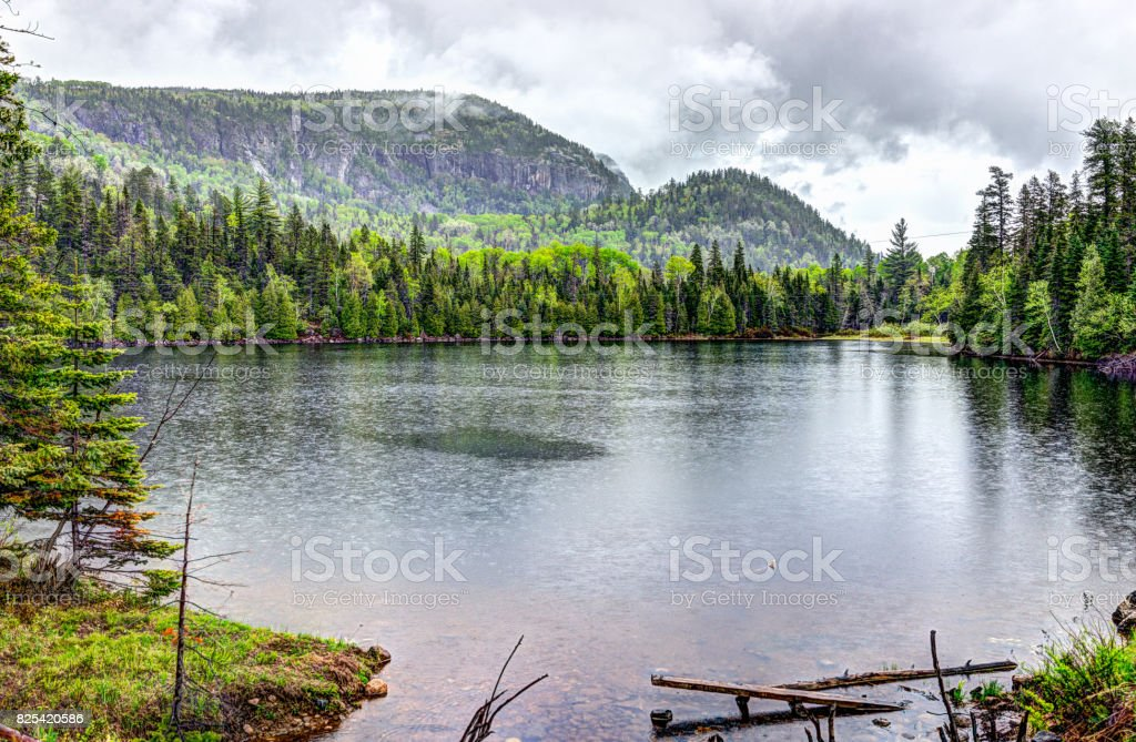 Lake water landscape by forest during rainy cloudy day in Quebec, Canada stock photo