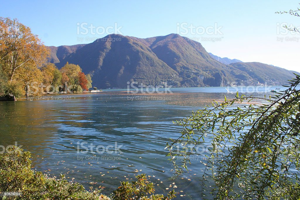 lake with vegetation and mountain in autumn colours stock photo