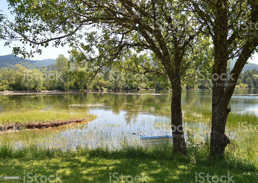 Lake with white rowboat on the bank stock photo