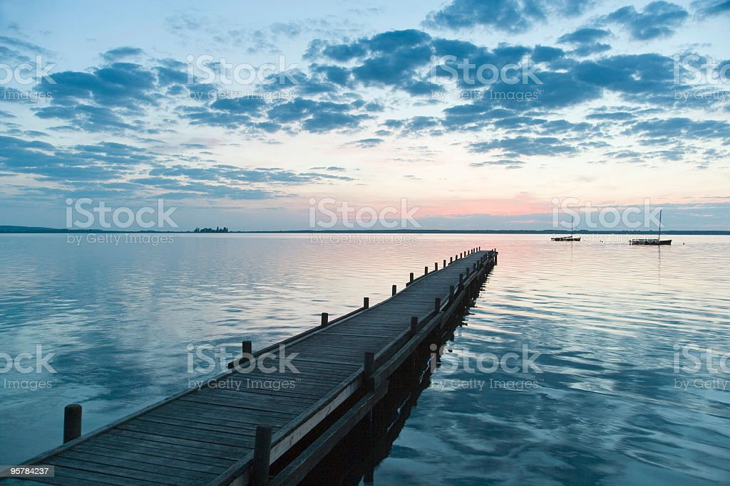 Lakeside jetty with magical cloudscape at dusk royalty-free stock photo