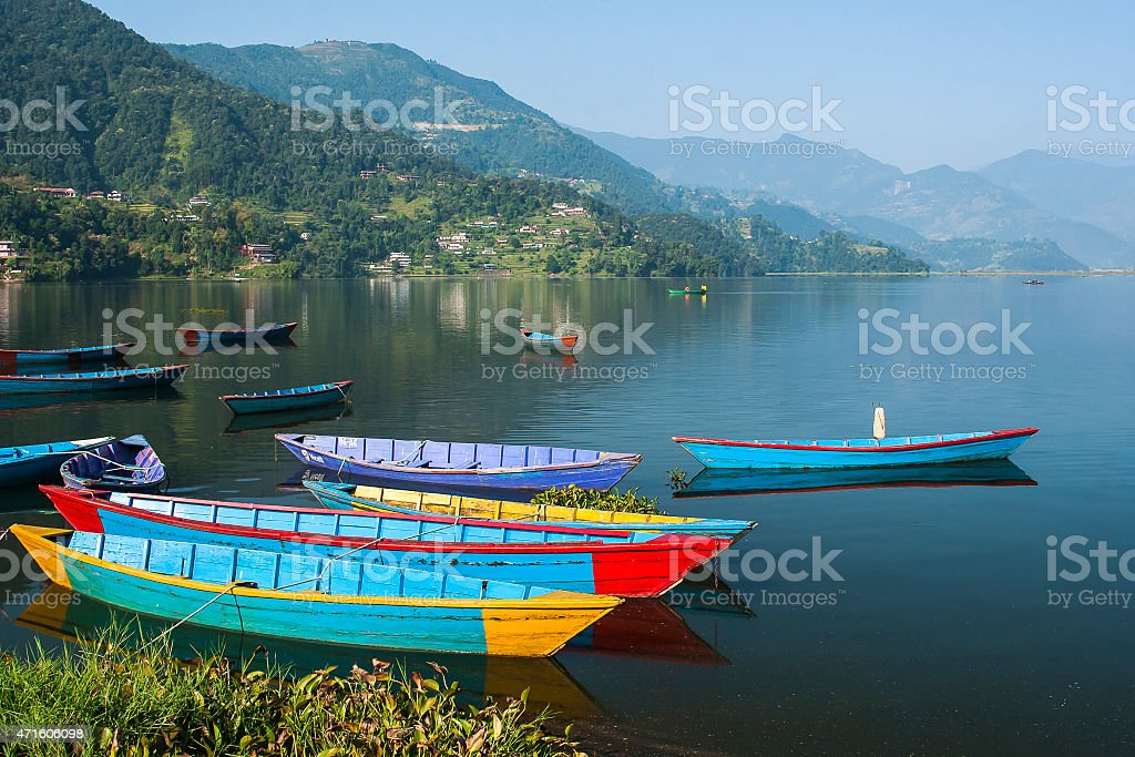 Lakeside overview of small colorful boats on lake Pokhara stock photo