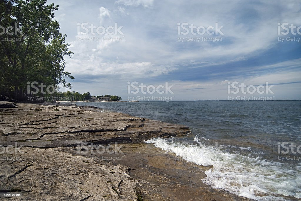 Lakeside view of waves, a rocky shoreline and cloudy sky stock photo