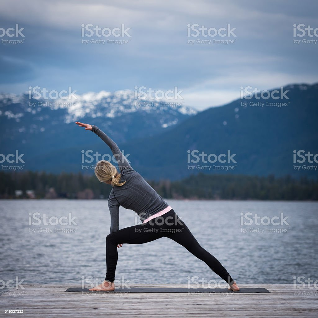 Lakeside yoga in the mountains stock photo