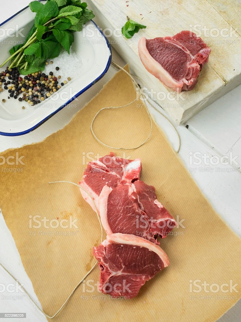 lamb chops  on brown paper with  herbs and spices behind stock photo