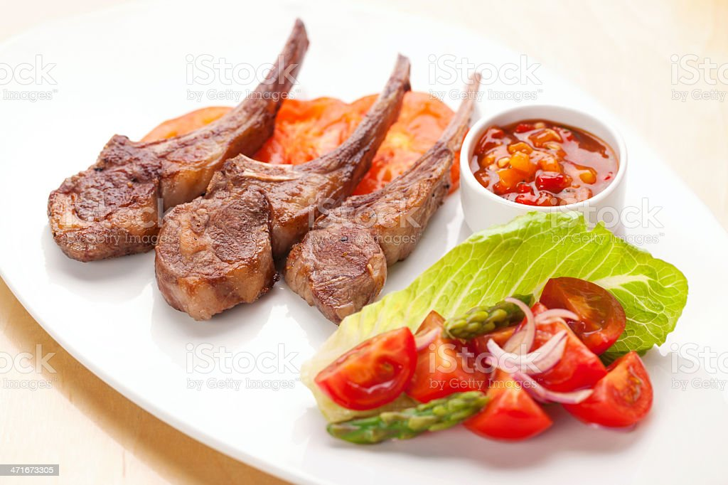 Lamb chops with asparagus salad and tomato salsa stock photo