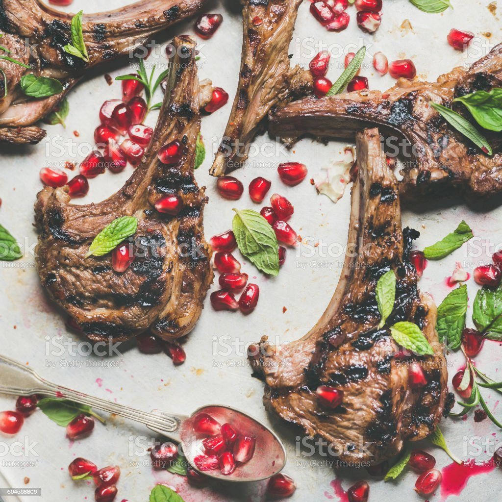 Lamb ribs barbecue with pomegranate seeds and herbs, square crop stock photo
