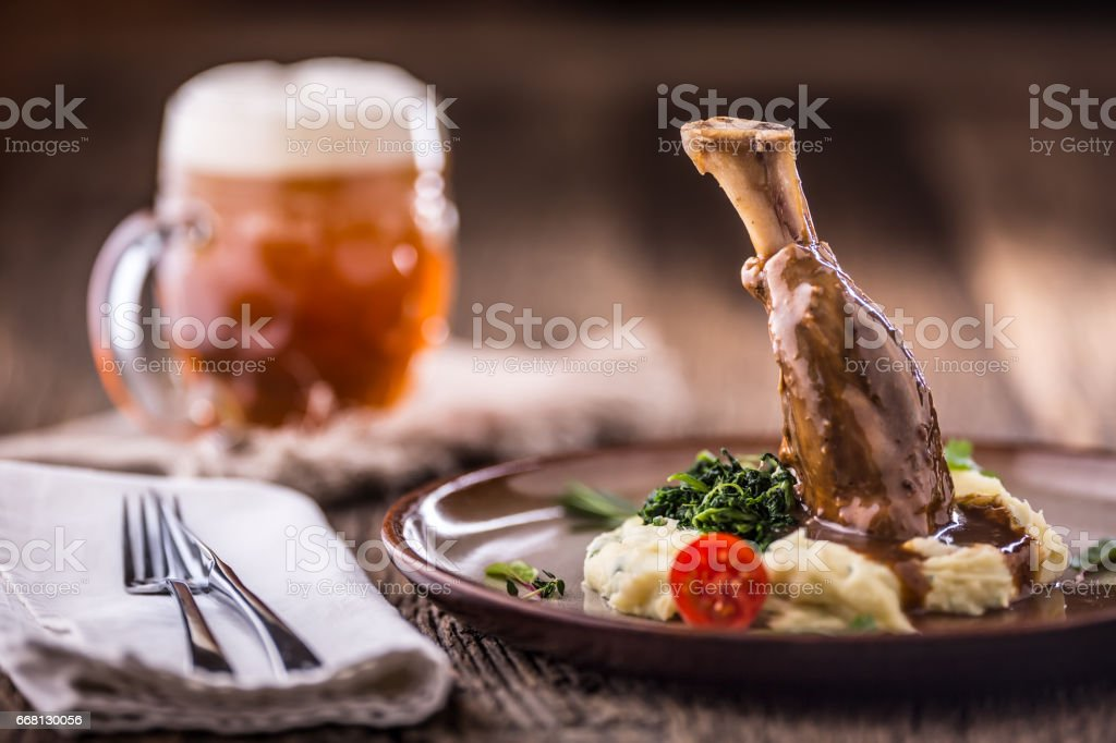 Lamb shank.Confit lamb shank with mashed potatoes spinach and draft beer in pup or restaurant stock photo
