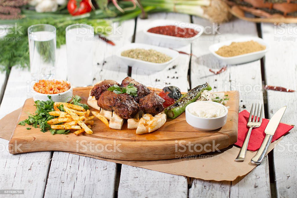 Lamb shish on wooden plate with fries stock photo