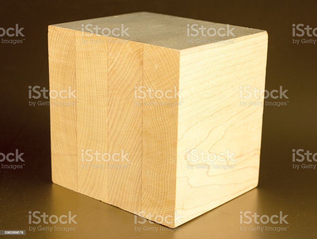 Laminated wood block on a gold background-  copy space stock photo