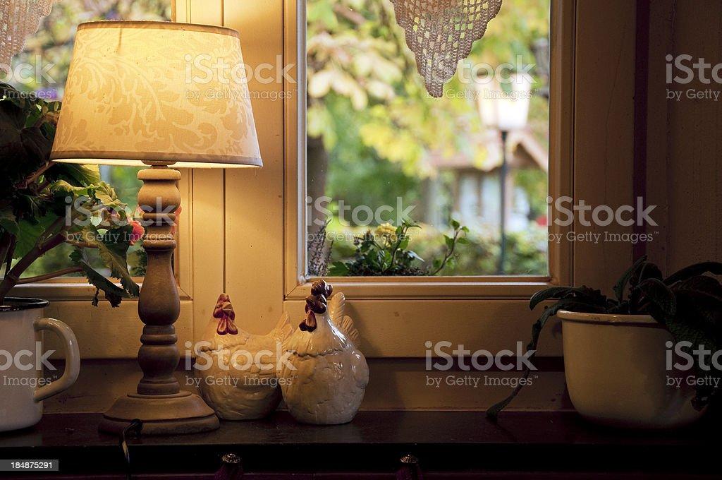 Lamp and ceramic chickens in windows sill stock photo