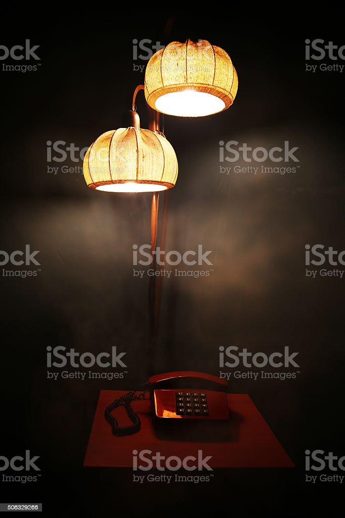 Lamp and red phone on table stock photo