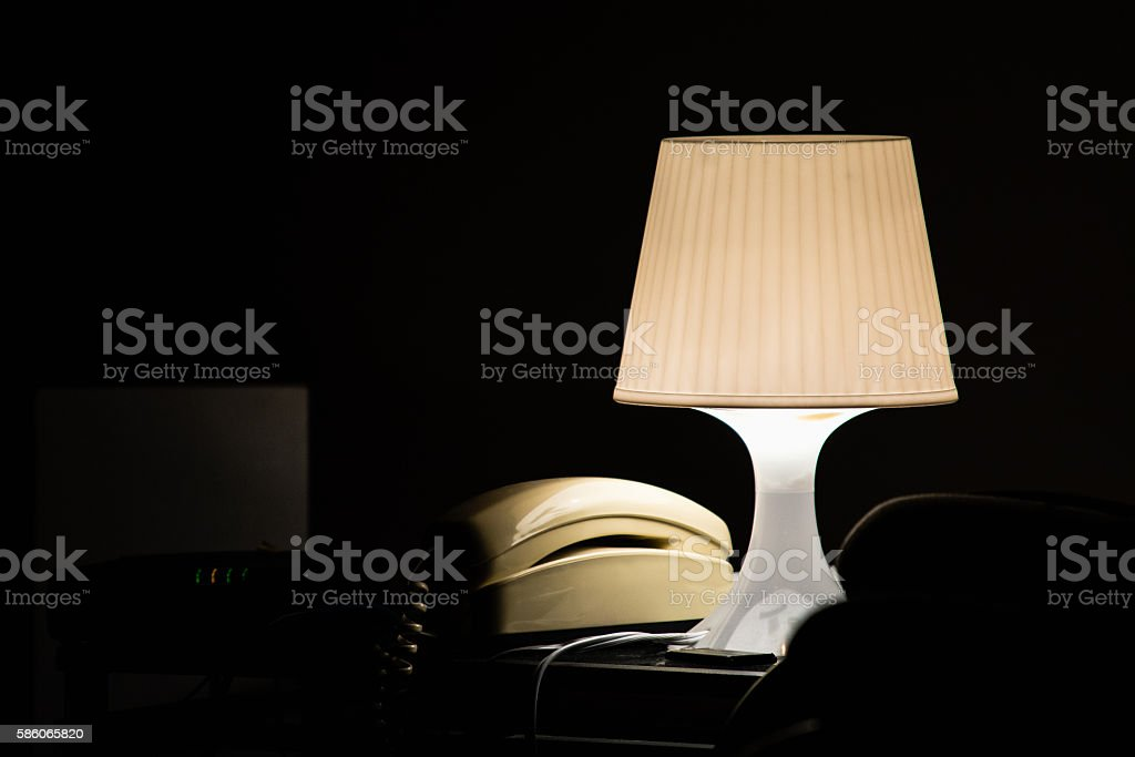 Lamp and telephone in a dark hotel room stock photo