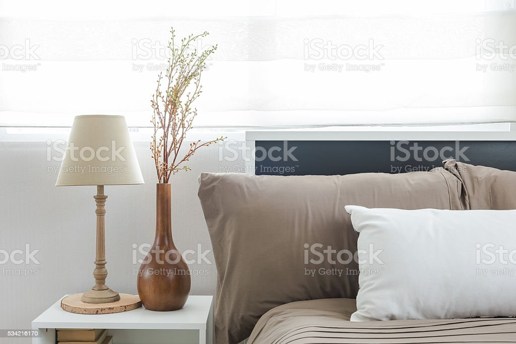 lamp and vase of flower on white table side stock photo