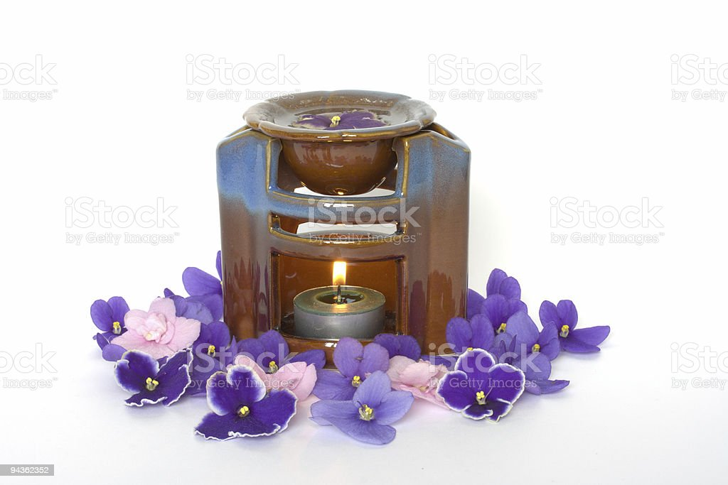 lamp for aromatherapy with candle and violet petals royalty-free stock photo