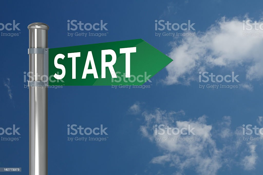 A lamp post with a green start sign placed outside stock photo