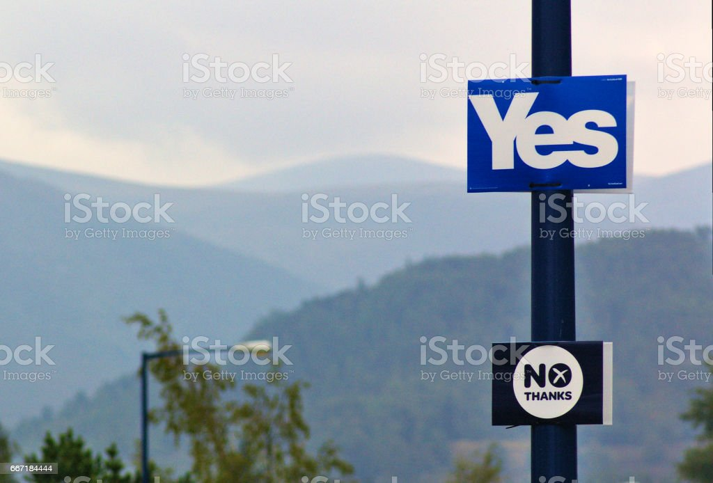 Lamp post with election posters of the referendum on Scottish independence saying 'Yes' and 'No', mountains, forest and trees stock photo
