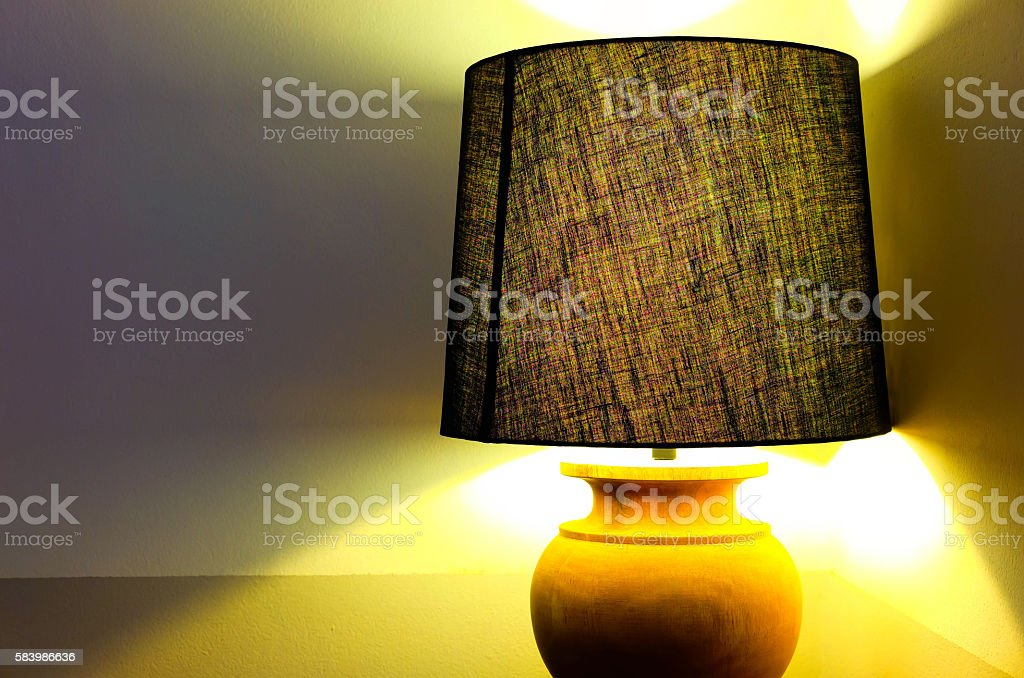 Lamp with Lampshade giving warm yellow light stock photo