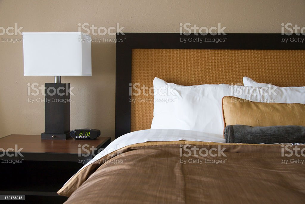 Lamp with white square shade and bed in brown and white stock photo
