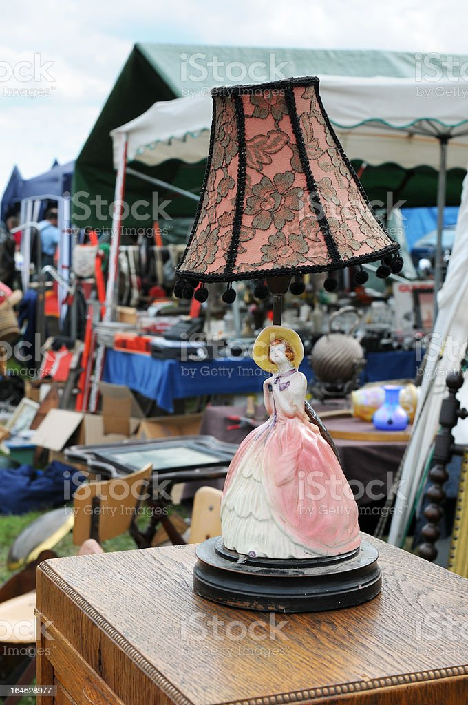 lamp with woman porcelain figure on cabinet at flea market stock photo