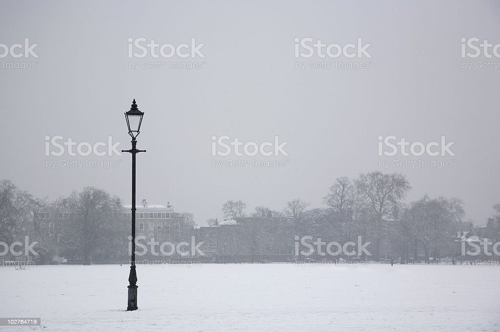 Lamppost in Snow Covered Park stock photo