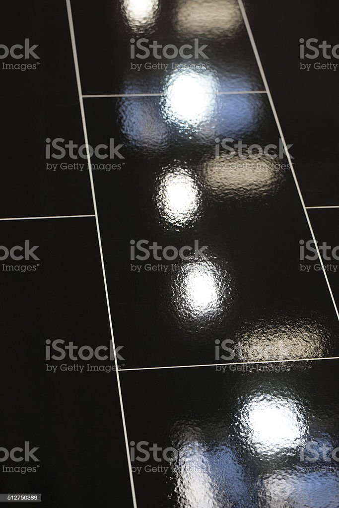 Lamps are reflected in the black tiled floor stock photo
