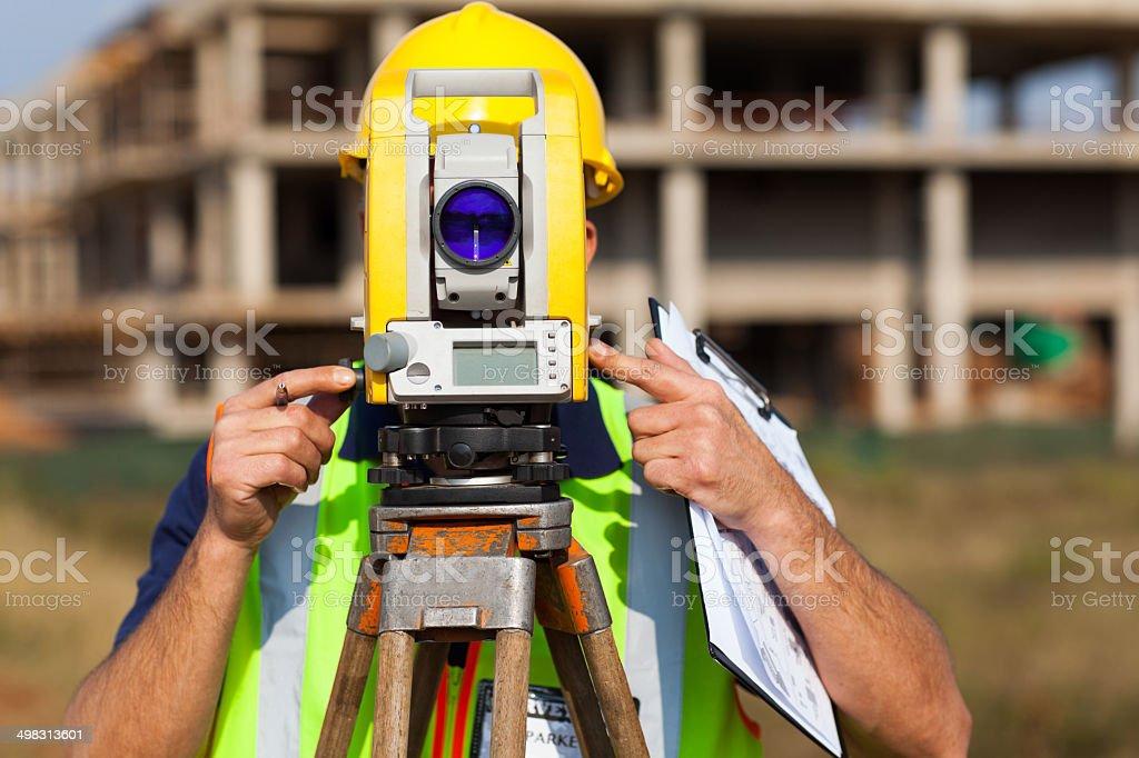 land surveyor looking through theodolite stock photo