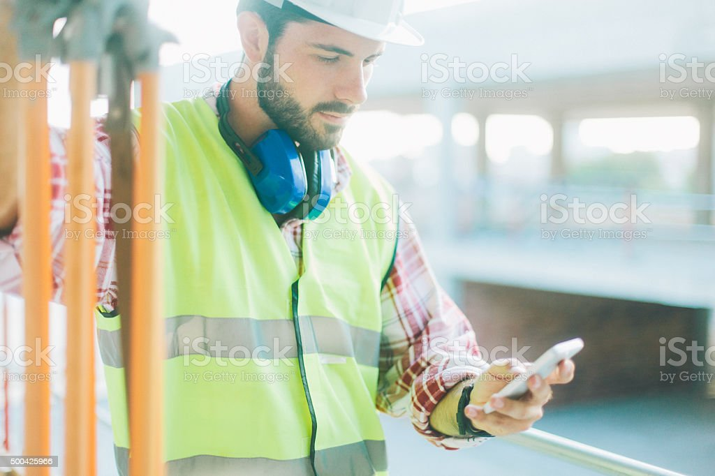 Land surveyor using app on smart phone. stock photo