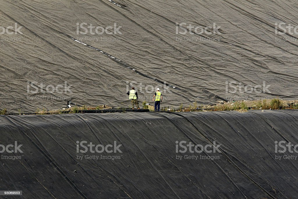 Landfill engineers inspecting rubber liner royalty-free stock photo