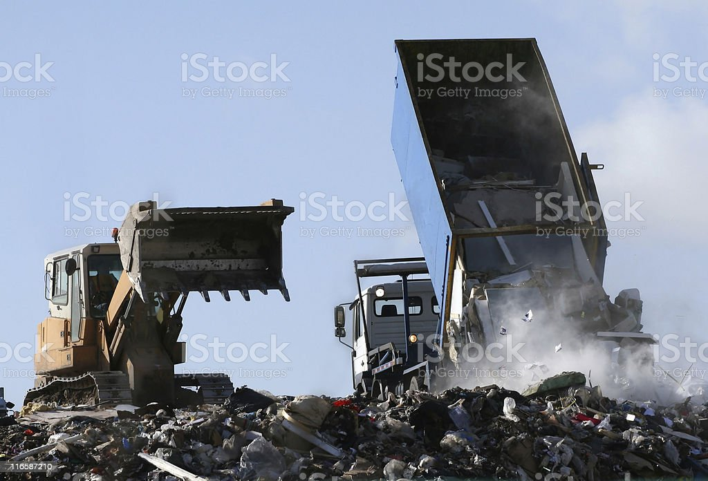 Landfill garbage bulldozer processing rubbish dumped by truck on site stock photo