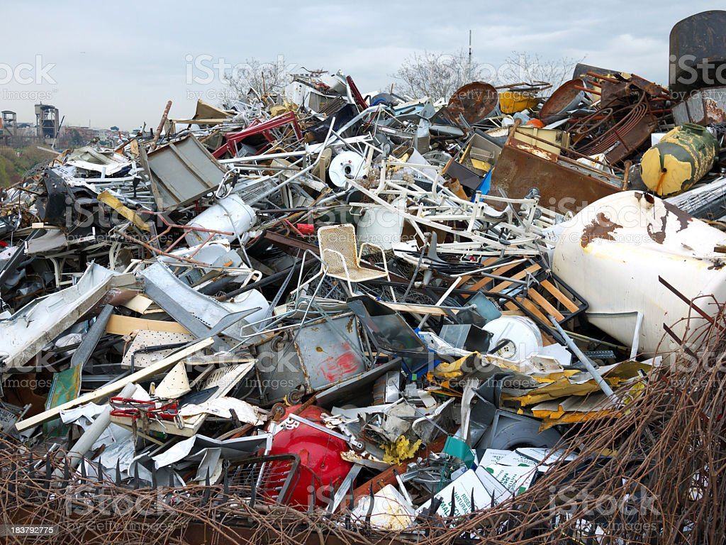 Landfill of metal household items under a gray sky stock photo
