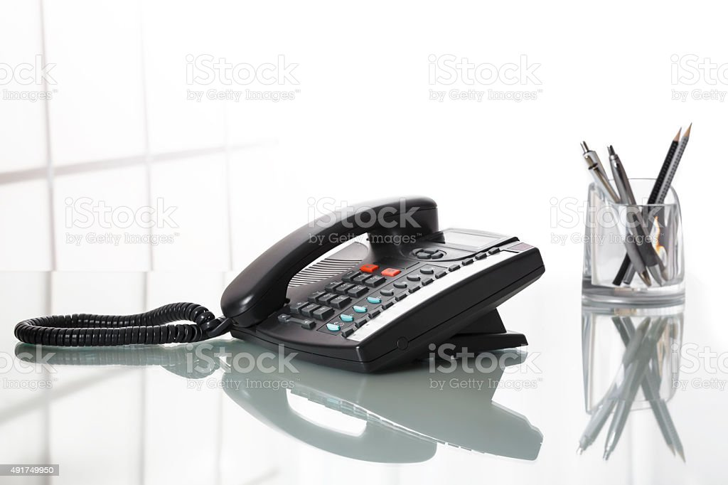 Landliine black phone on an office desk. stock photo