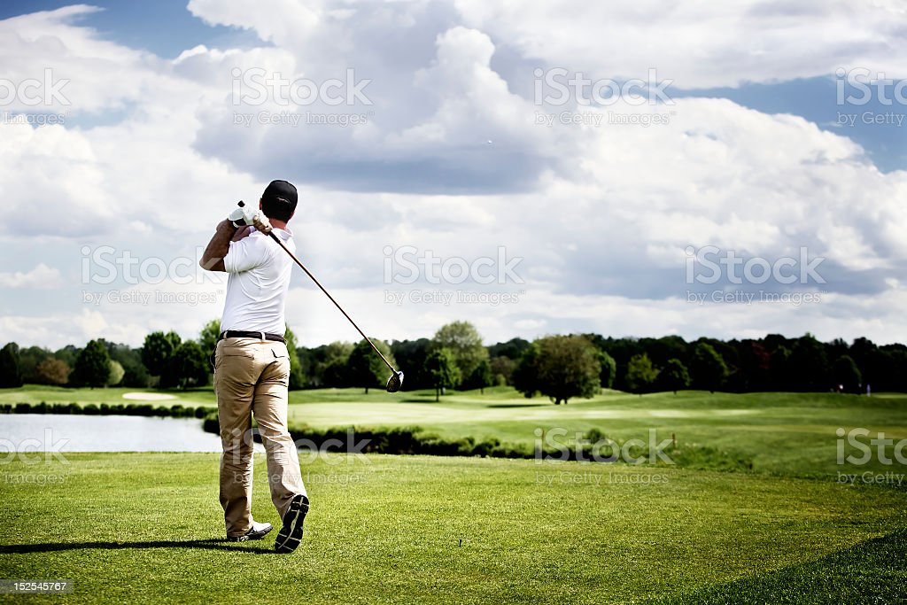 A landscape focusing on a golf player mid-swing stock photo