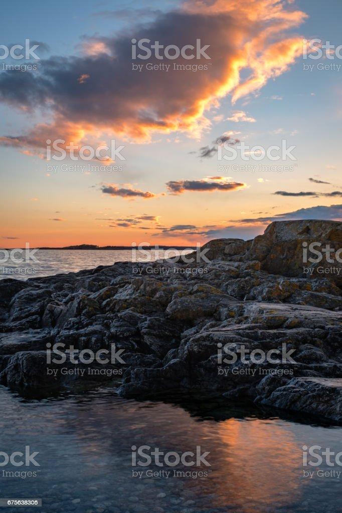 Landscape image of clouds lighting up over rocks during sunset at...