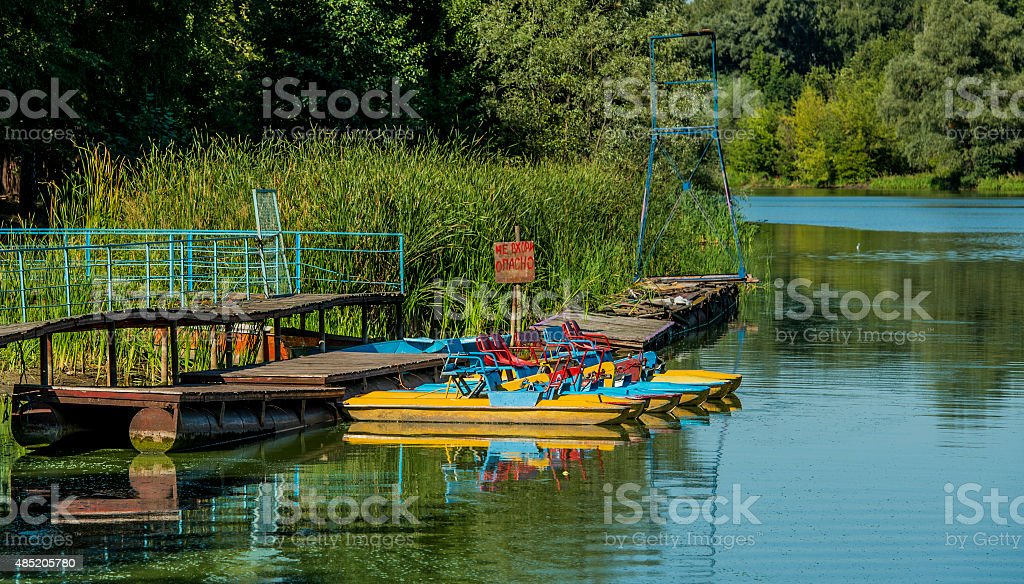 Landscape lake with pedal boats on the shore stock photo