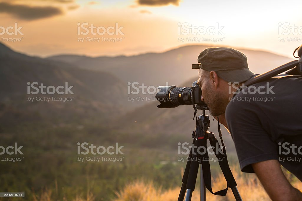 Landscape male photographer in action taking picture stock photo