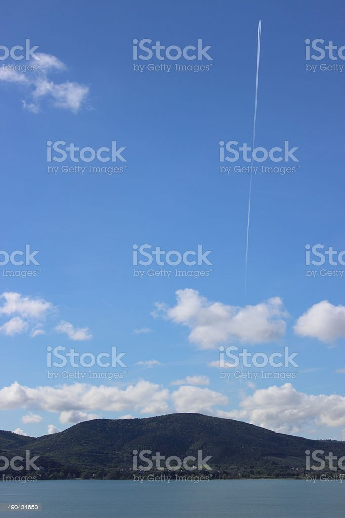 landscape of a lake with a contrail of airplane stock photo