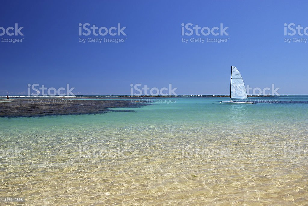 Landscape of a tropical beach with a sailboat stock photo