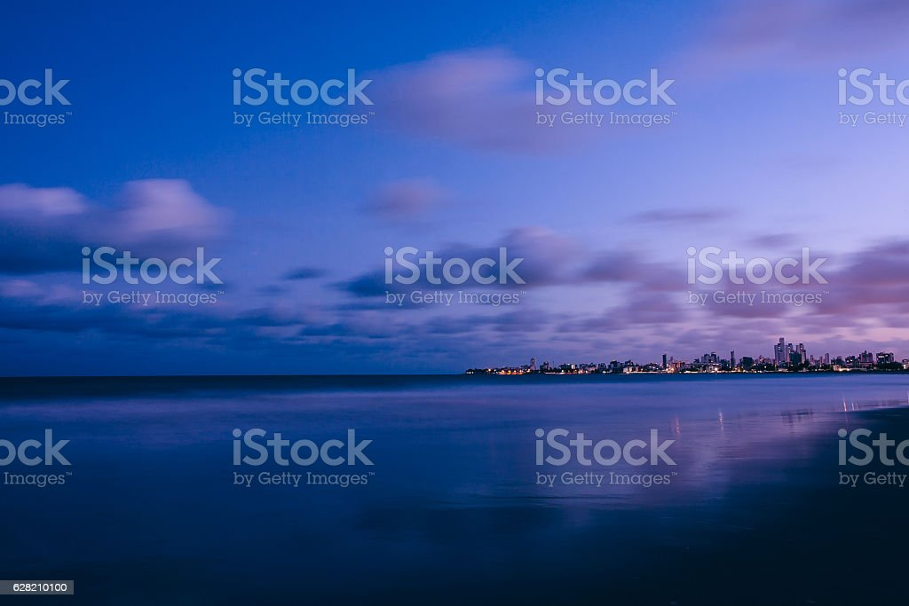 Landscape of an urban beach after sunset with purple sky stock photo