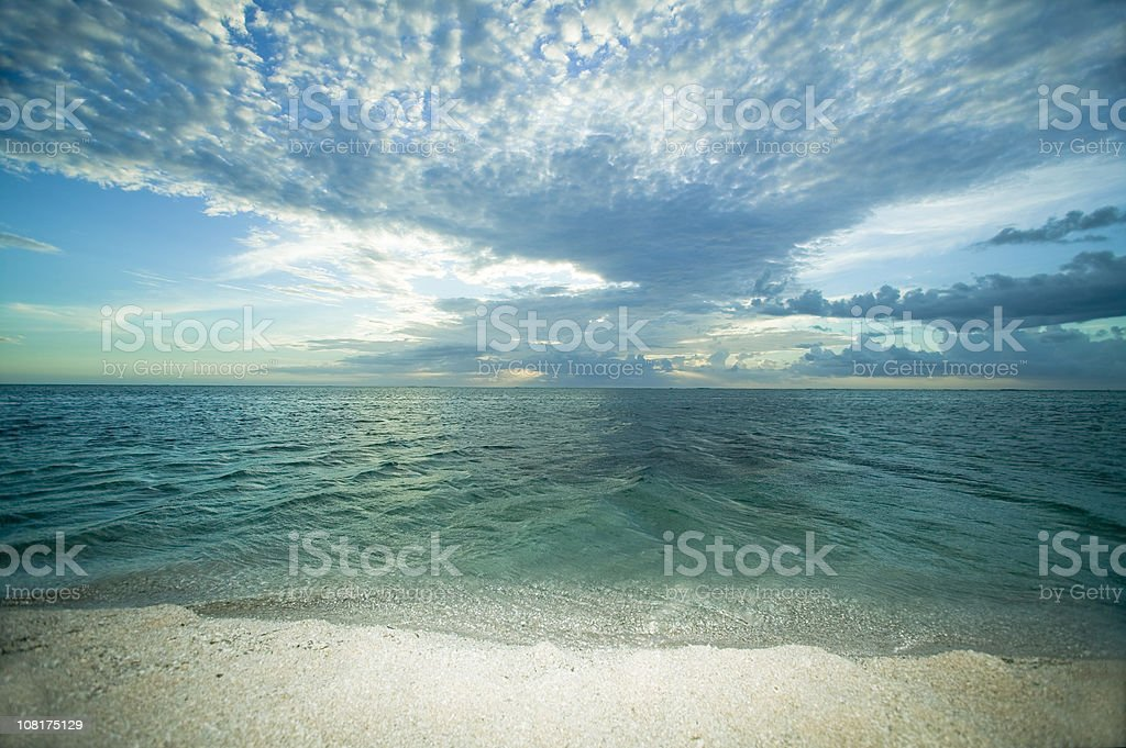 Landscape of Beach and Water's Edge with Clouds in Sky stock photo