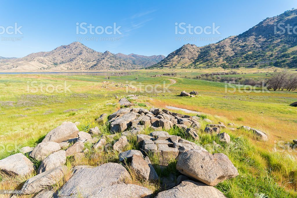 landscape of green grass, rock and mountain stock photo