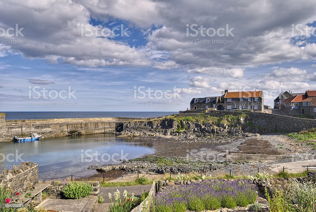 Landscape of houses and boat at Craster Harbour stock photo
