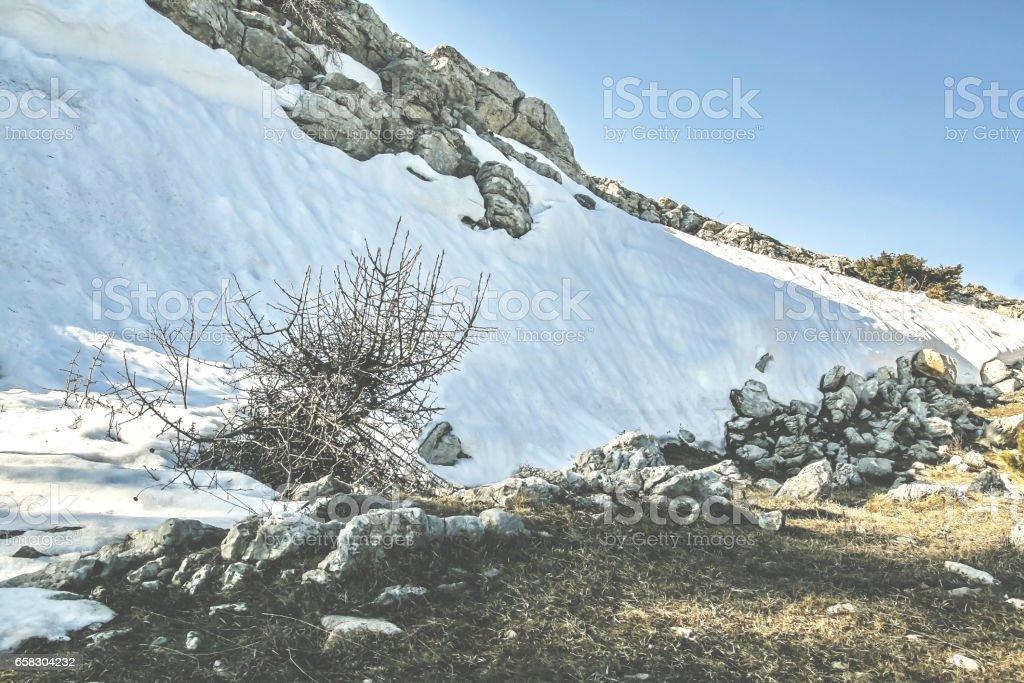 Landscape on the mountain stones, snow, under the bright sun, in retro style stock photo