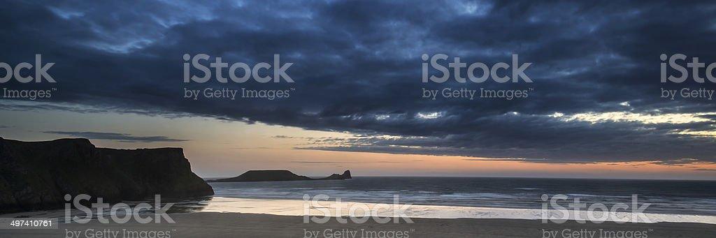 Landscape panorama Rhosilli Bay beach at sunset with moody sky stock photo