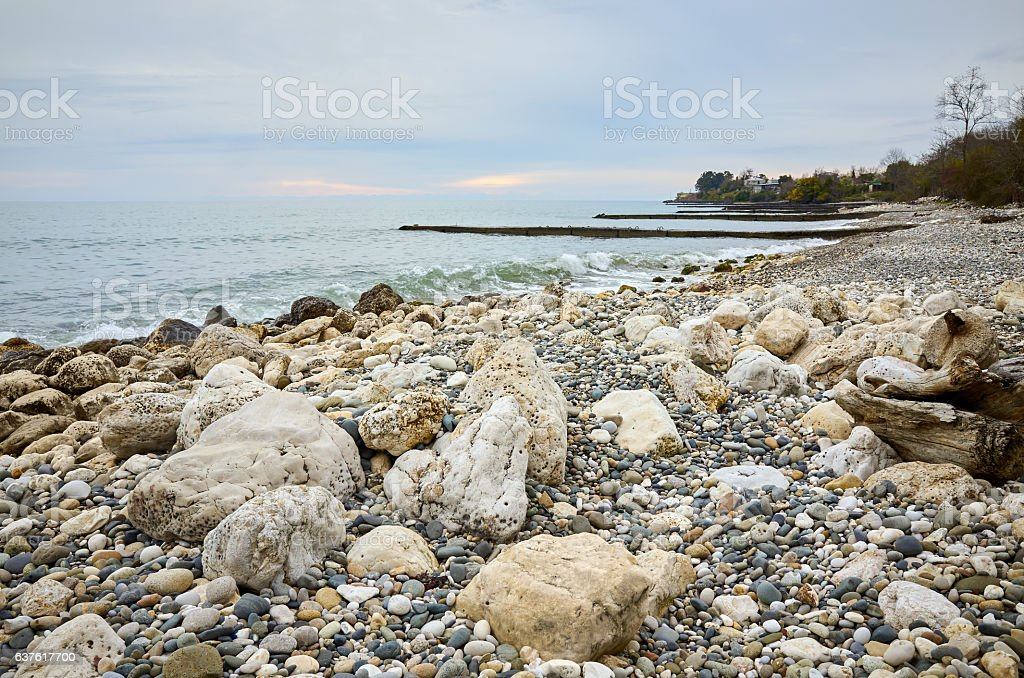 Landscape stone beach Black sea, New Athos, blue cloudy sky stock photo