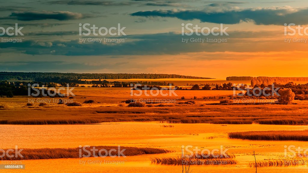 Landscape sunset river meadows field forest hills lit by orange stock photo